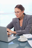 Verticale d'une femme d'affaires orientée à l'aide d'un ordinateur portable Photographie stock libre de droits