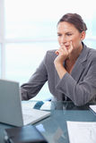 Verticale d'une femme d'affaires réfléchie travaillant avec un ordinateur portable photo stock