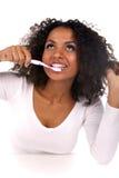Verticale d'une femme de couleur nettoyant ses dents Image libre de droits