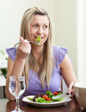 Verticale d'une femme gaie mangeant d'une salade photographie stock