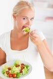 Verticale d'une femme mangeant d'une salade Image libre de droits