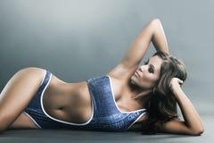 Verticale d'une femme menteuse magnifique dans le bikini bleu images libres de droits