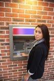 Verticale d'une femme retirant l'argent comptant photographie stock