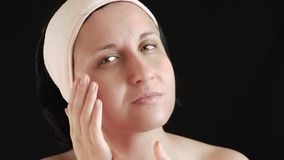 Verticale d'une femme sur un profil noir de background La fille applique les produits faciaux de soin : tonique, sérum, crème et  banque de vidéos