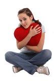 Verticale d'une fille étreignant un grand coeur rouge de peluche Photographie stock