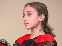 Verticale d'une fille avec les boucles d'oreille espagnoles et la robe rouge avec le lacet noir photographie stock libre de droits