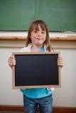 Verticale d'une fille de sourire retenant une ardoise d'école Images stock