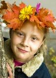 Verticale d'une fille s'usant une guirlande de leav d'automne Image libre de droits