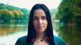 Verticale d'une jeune femme avec le cheveu noir Femme près du lac au coucher du soleil du jour Une fille avec des fossettes banque de vidéos