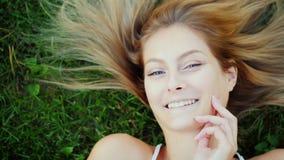 Verticale d'une jeune femme avec le long cheveu Elle se trouve sur la pelouse, ses mensonges de cheveux admirablement sur l'herbe Image stock