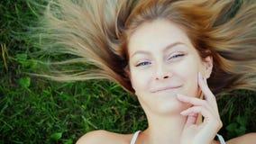 Verticale d'une jeune femme avec le long cheveu Elle se trouve sur la pelouse, ses mensonges de cheveux admirablement sur l'herbe Photos stock