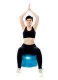 Verticale d'une jeune fille s'asseyant sur la bille gymnastique Images stock