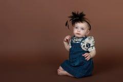 Verticale d'une jeune fille sur le fond brun Photographie stock libre de droits