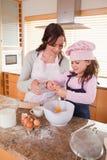 Verticale d'une mère et de sa cuisson heureuse de descendant Photo stock