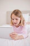 Verticale d'une petite fille à l'aide d'un ordinateur de tablette images libres de droits