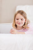 Verticale d'une petite fille de sourire à l'aide d'un ordinateur de tablette photo libre de droits