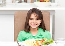 Verticale d'une petite fille mangeant des pâtes et de la salade Photographie stock