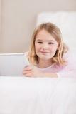 Verticale d'une petite fille mignonne à l'aide d'un ordinateur de tablette image libre de droits