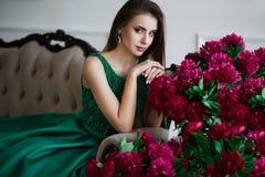 Verticale de beauté La belle femme avec les lèvres marron sensuelles se trouvant parmi la pivoine fleurit Cosmétiques, maquillage image stock