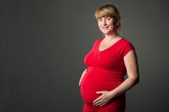 Verticale de belle femme enceinte dans la robe rouge Images libres de droits