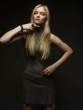 Verticale de belle jeune fille blonde dans la robe noire images stock