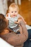 Verticale de chéri gaie jouant sur des genoux de mamans Photographie stock
