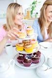 Verticale de deux amis mangeant des pâtisseries dans le ki Photo stock