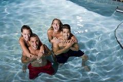 Verticale de deux couples dans la piscine la nuit Photos libres de droits