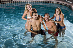 Verticale de deux couples dans la piscine la nuit Images libres de droits