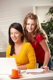 Verticale de deux filles avec l'ordinateur portatif Image libre de droits