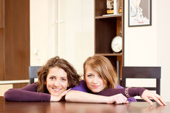 Verticale de deux filles s'asseyant sur une table de cuisine Photos libres de droits
