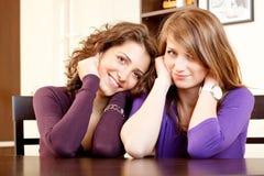 Verticale de deux filles s'asseyant sur une table de cuisine Photos stock
