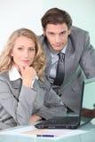 Verticale de deux gens d'affaires avec l'ordinateur portatif Photographie stock libre de droits