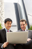 Verticale de deux hommes d'affaires travaillant sur l'ordinateur portatif Photographie stock libre de droits