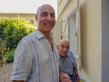 Verticale de deux hommes Le fils plus âgé soutient son vieux père et aide le sien images libres de droits