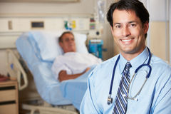 Verticale de docteur With Patient In Background Photographie stock