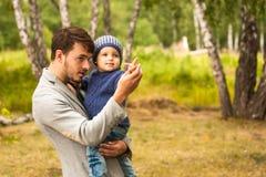 Verticale de famille Jeu de père avec son enfant Père tenant un enfant dans des ses bras Ils sont heureux Marche heureuse de fami Photographie stock