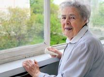 Verticale de femme aînée à l'hublot image libre de droits