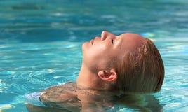 Verticale de femme détendant dans la piscine photographie stock