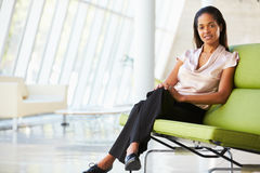 Verticale de femme d'affaires se reposant sur le sofa dans le bureau moderne Photos stock