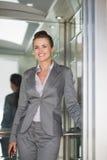 Verticale de femme de sourire d'affaires dans l'ascenseur Photo libre de droits