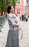 Verticale de femme de sourire de brunette en ville Photographie stock