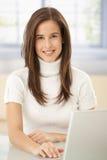 Verticale de femme intelligente avec l'ordinateur Photographie stock libre de droits