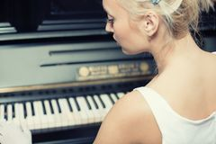 Verticale de femme jouant sur le rétro piano de type photographie stock libre de droits