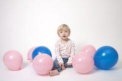 Verticale de fille mignonne avec les ballons roses et bleus Images libres de droits