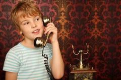 Verticale de garçon parlant à un vieux téléphone Photo libre de droits