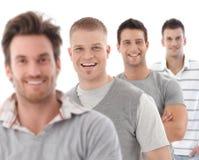 Verticale de groupe de jeunes hommes heureux photos stock