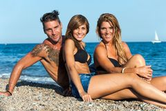 Verticale de groupe des amis s'asseyant sur la plage. Photo stock