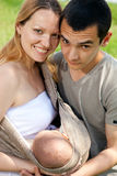 Verticale de jeune famille avec la chéri dans l'élingue Image libre de droits