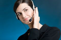 Verticale de jeune femme avec l'écouteur, sur le fond bleu, souriant Image libre de droits